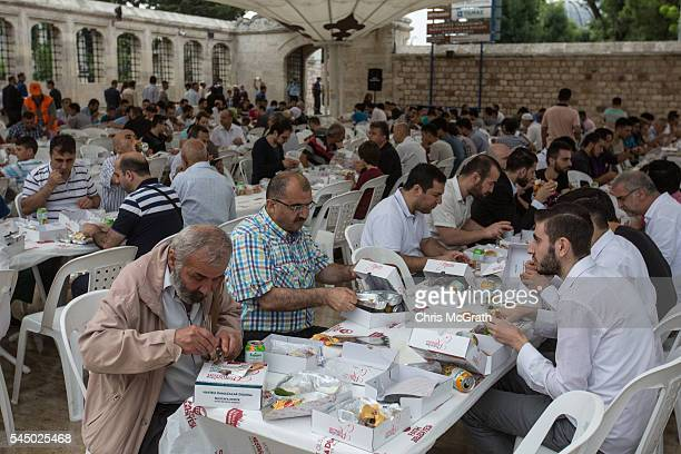 Turkish Muslims enjoy free meals distributed after attending Eid al Fitr prayers as they mark the first day of the Eid alFitr at Fatih Sultan Mosque...