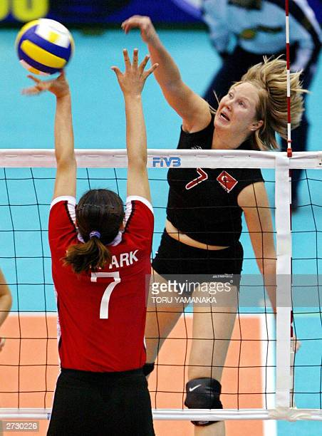 Turkish Natalia Hanikoglu spikes the ball over Park MeeKyung of South Korea during the final round match in the World Cup women's volleyball...