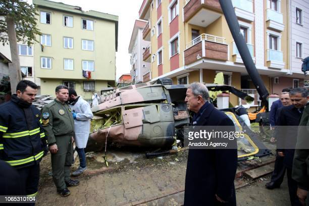 Turkish National Defense Minister Hulusi Akar inspects the wreckage after a military helicopter crashed in a residential area in Istanbuls Sancaktepe...