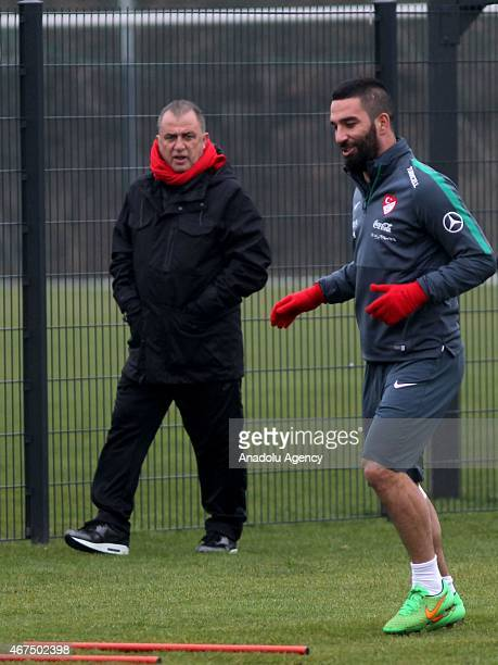 Turkish National Team's head coach Fatih Terim is seen as Arda Turan of Turkey exercises during the training session ahead of UEFA Euro 2016...