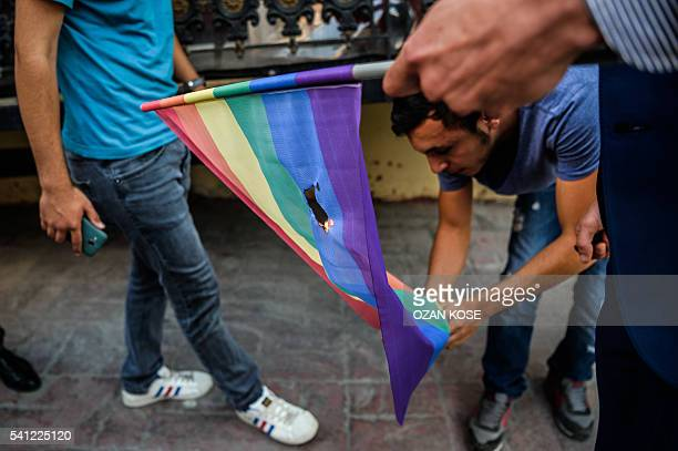 Turkish nationalists burn a rainbow flag during a rally staged by the LGBT community on Istiklal avenue in Istanbul on June 19 2016 Turkish riot...