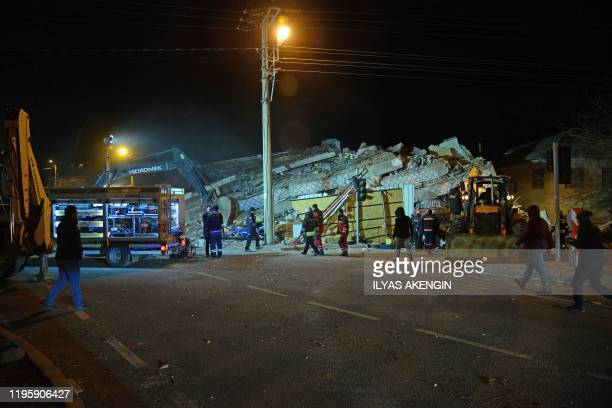 Turkish officials and police work at the scene of a collapsed building following a 68 magnitude earthquake in Elazig eastern Turkey on January 24...