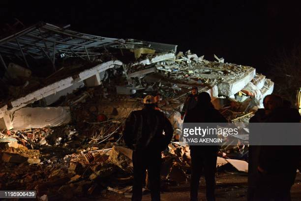TOPSHOT Turkish officials and police work at the scene of a collapsed building following a 68 magnitude earthquake in Elazig eastern Turkey on...