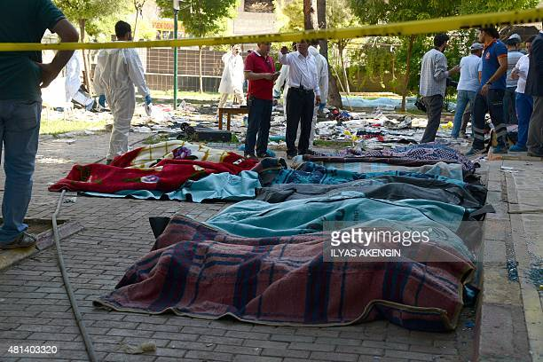 Turkish officials work on the site of an explosion in the town of Suruc not far from the Syrian border on July 20 2015 At least 30 people were killed...