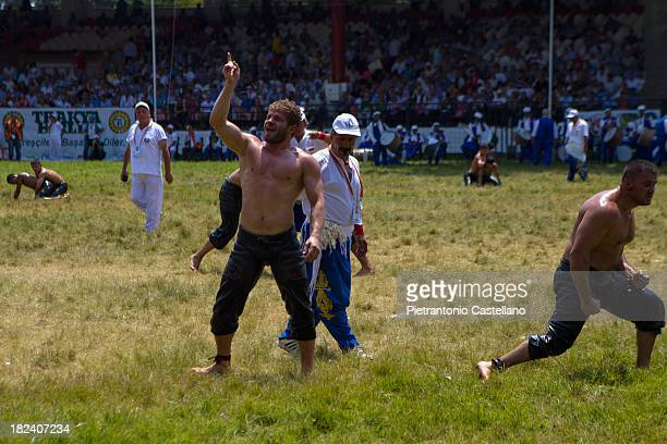 "Turkish oil wrestler is victorious while his adversary walks away in frustration in the annual tournament known as ""Kirkpinar"" in Edirne, Turkey."