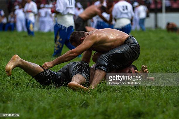 Turkish oil wrestler locks the adversary on the ground, in what is going to be the final move of the match.
