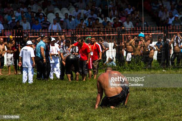 Turkish oil wrestler stays where he fell while the adversary who beat him is celebrated.