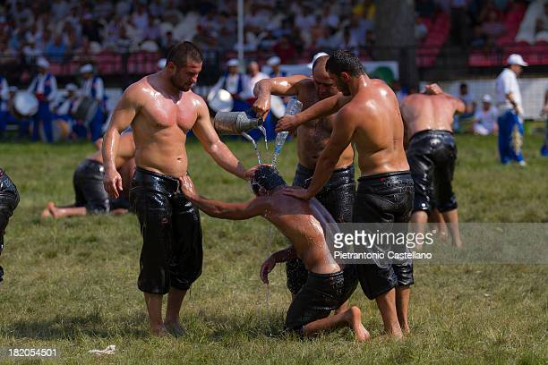 Turkish Oil Wrestlers console a fellow athlete after his defeat, refreshing him with water.