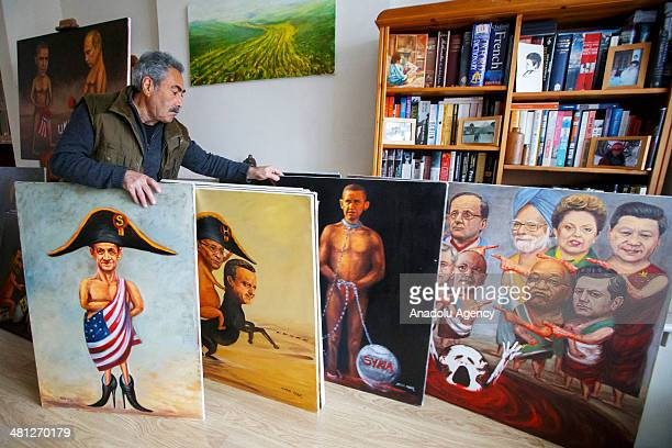 Turkish painter Maya Mar demonstrates some of his satirical works in his atelier in London, England on March 25, 2014. Kaya Mar, a renowned Turkish...