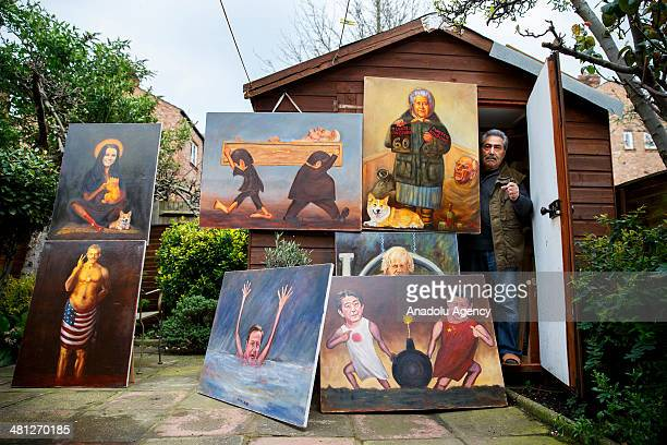 Turkish painter Maya Mar poses with some of his satirical works in his atelier in London, England on March 25, 2014. Kaya Mar, a renowned Turkish...