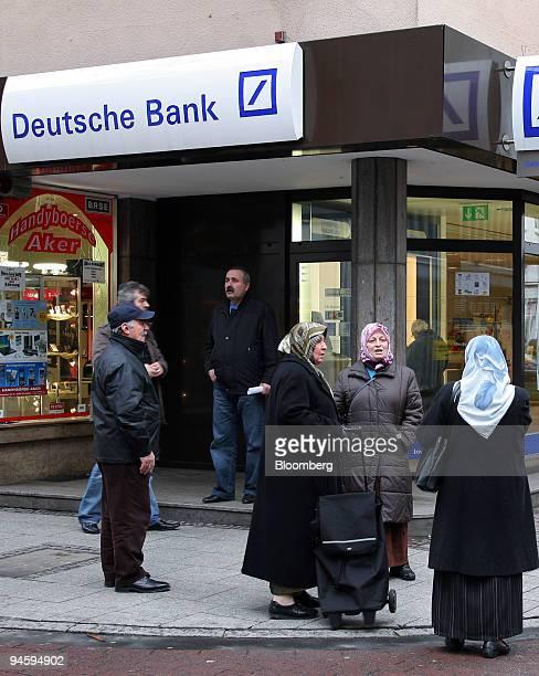 Turkish Pedestrians stand outside at a Deutsche Bank branch in Frankfurt-Hoechst, Germany, on Wednesday, Jan. 16, 2008. Deutsche Bank AG, Germany's...