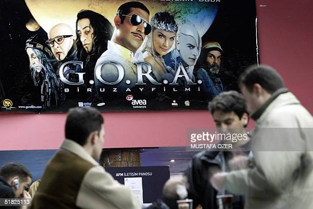Turkish people drink coffee in front of AFM cinema in Istanbul showing G.O.R.A., a home-made movie breaking box office hits in Turkey, 24 November...