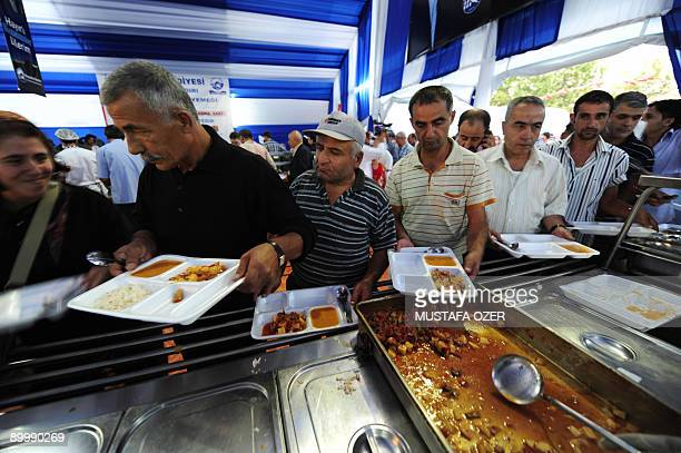 Turkish people receive food in front of a tent pitched up for poor people for the evening meal of Ramadan Muslims' holy month in Eminonu downtown...