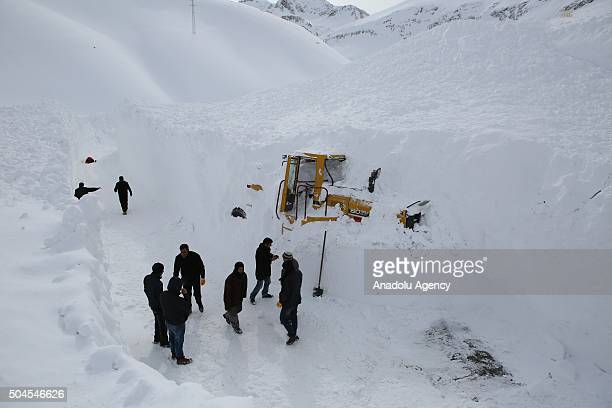 Turkish people try to rescue a Caterpillar which was buried under avalanche at highway Bahcesaray Van highway in Turkey on January 11 2016