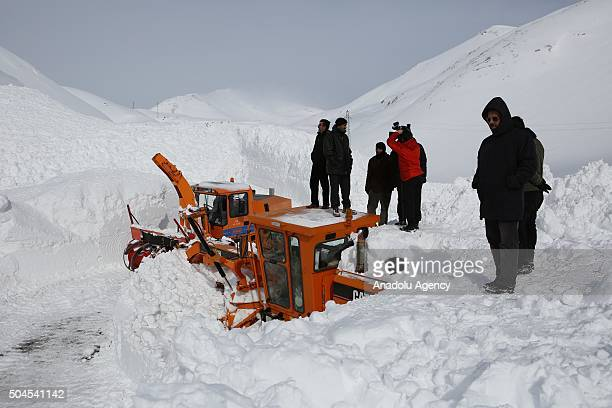 Turkish people waits in front of Caterpillar which was buried under avalanche at highway Bahcesaray - Van highway in Turkey on January 11, 2016.