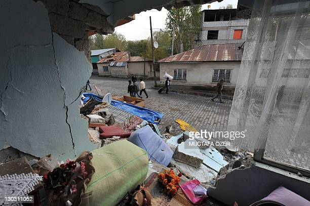 Turkish people walk in front of a collapsed building after an earthquake in Ercis province of Van on October 26 2011 Homeless survivors of Turkey's...