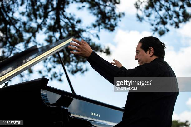 Turkish pianist and composer Fazil Say gives a performance against deforestation on the site of a controversial goldmine project near the town of...