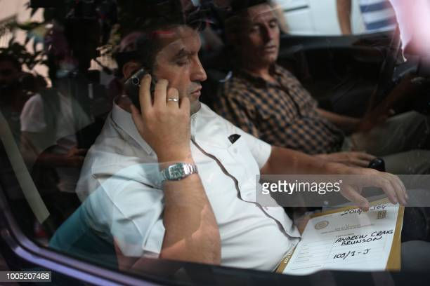 A Turkish plain clothes police officer talks to his phone in a car as he holds a file reading the name of US pastor Andrew Brunson who arrives at his...