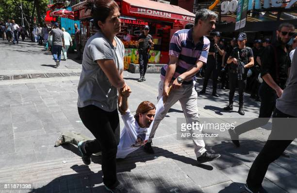 Turkish plainclothes police officers detain a protester during a demonstration in support of two hungerstrikers in Ankara on July 10 2017 Turkish...