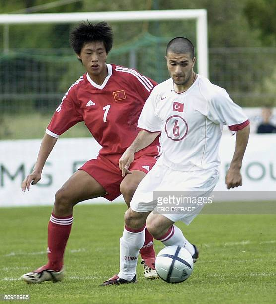 Turkish players Adem Kocak fights for the ball with Chinese player Shouting Wang 05 June 2004, at Cauvin stadium in Lorgues, during the under 21's...