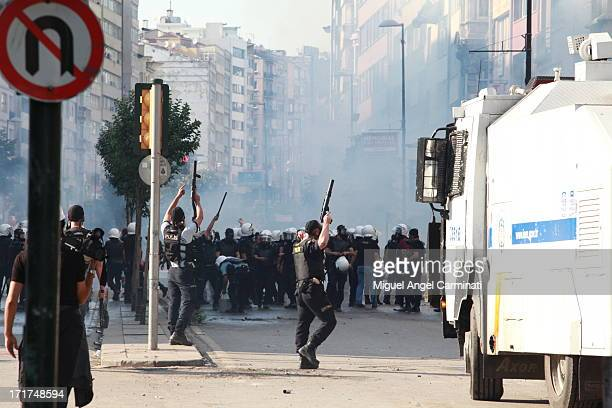 Turkish police celebrating after taking a corner where protestors were standing. In the background a tear gas cloud.