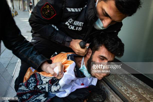 Turkish police detain a demonstrator as they clash during a May Day rally marking the international day of the worker in Istanbul, on May 1, 2021. -...