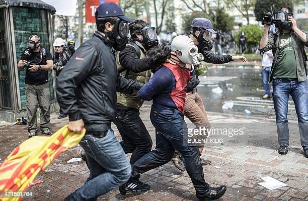 Turkish police detain a protestor wearing a gas mask during a May Day rally near Taksim Square in Istanbul on May 1 2015 Turkish police on used tear...