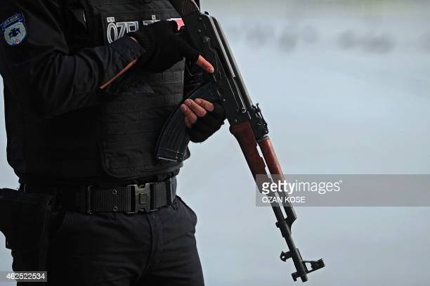 A Turkish police officer armed with an AK47 stands guard near the site where shots were fired at a police post off Taksim Square in Istanbul on...