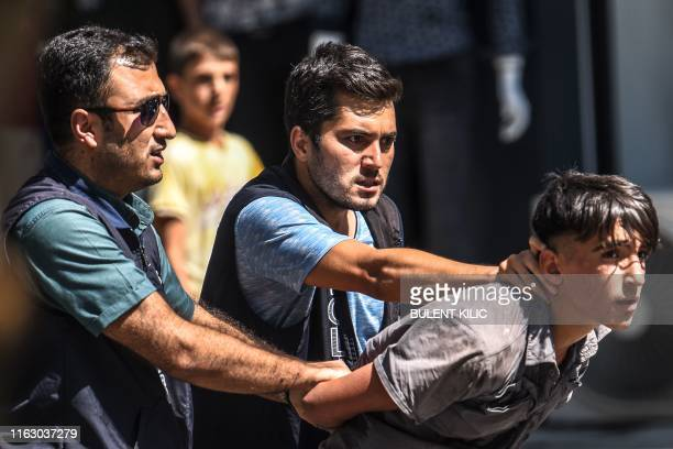 Turkish police officer detain a demonstrator during a protest against the replacement of Kurdish mayors with state officials in three cities, in...