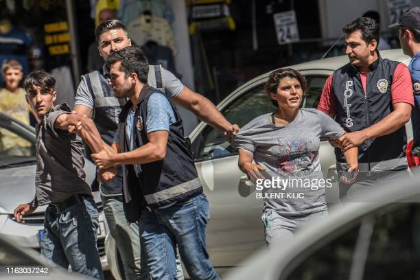 Turkish police officer detain demonstrators during a protest against the replacement of Kurdish mayors with state officials in three cities, in...
