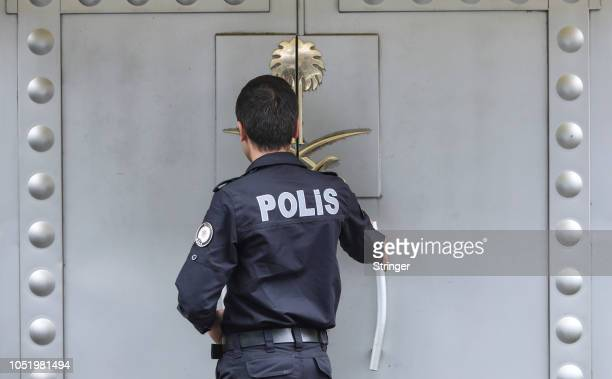 Turkish police officer providing security enters the Saudi Arabia's consulate as they check papers of a man on October 12 2018 in Istanbul Turkey...