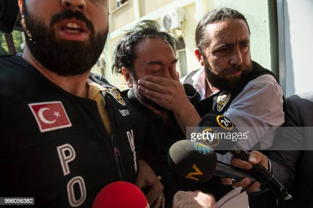 A Turkish police officer puts his hand on the face of televangelist and leader of a sect Adnan Oktar as he escorts him on July 11 in Istanbul...