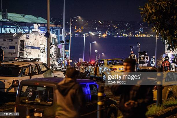Turkish police officers and forensic work next to damaged police vehicles and cars on the site where a car bomb exploded near the stadium of football...