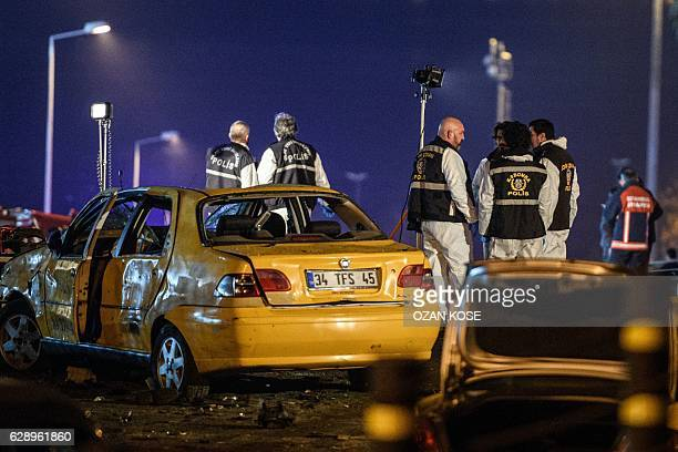 Turkish police officers and forensic work on the site where a car bomb exploded near the stadium of football club Besiktas in central Istanbul on...