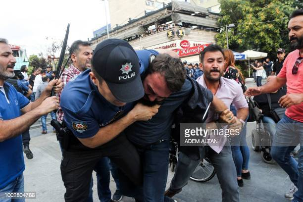 Turkish police officers arrest a man, in Ankara, on July 20, 2018 as he was taking part in a demonstration for the anniversary of the 2015 suicide...