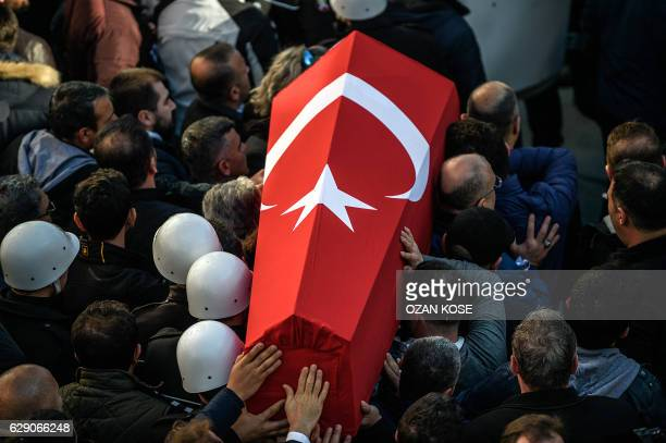 TOPSHOT Turkish police officers carry the coffins of a comrade during a funeral ceremony at Istanbul's police headquarters on December 11 a day after...