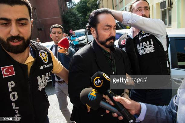 Turkish police officers escort televangelist and leader of a sect Adnan Oktar on July 11 in Istanbul as he is arrested on fraud charges Turkish...