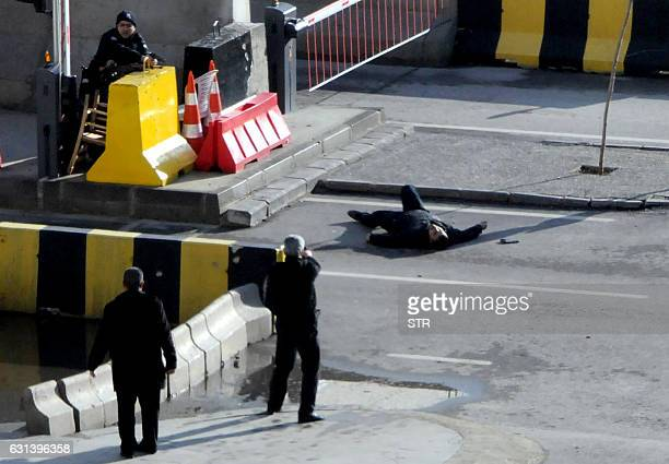TOPSHOT Turkish police officers point their weapons at a man lying on the ground after they shot him outside a Turkish police station in Gaziantep on...