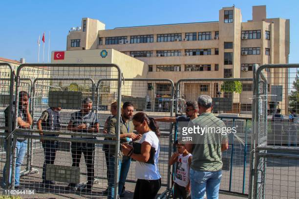 Turkish police officers put barriers and stand guard in front of the Metropolitan Municipality headquarters entrance in Diyarbakir, on August 19,...