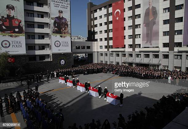 Turkish police officers stand guarded near the flagdraped coffins of police officers killed in yesterday's blast on December 11 2016 in Istanbul...