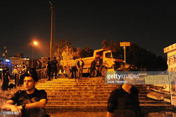 Turkish police stand guard at the entrance of Gezi Park as municipal workers begin cleaning the protest site, after police recaptured the park near...