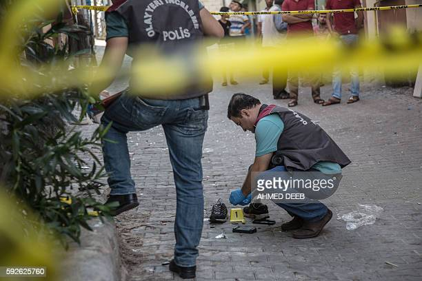 Turkish police work near the explosion scene following a late night attack on a wedding party that left at least 30 dead in Gaziantep in southeastern...