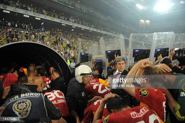 Turkish policemen protect Galatasaray's players after their victory over Fenerbahce at the end of their Turkish Super League playoff final football...