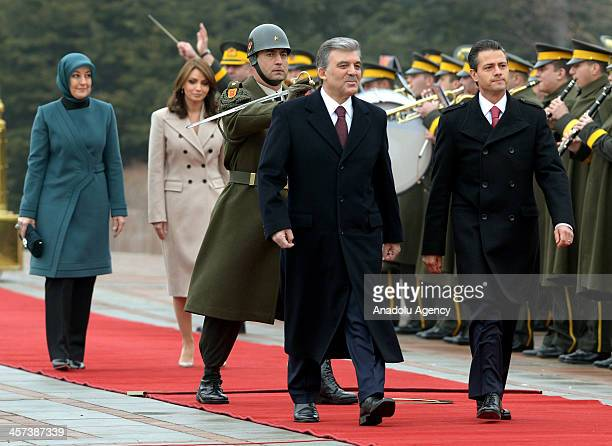 Turkish President Abdullah Gul and his Mexican counterpart Enrique Pena Nieto review a military honour guard with their wifes Hayrunnisa Gul and...