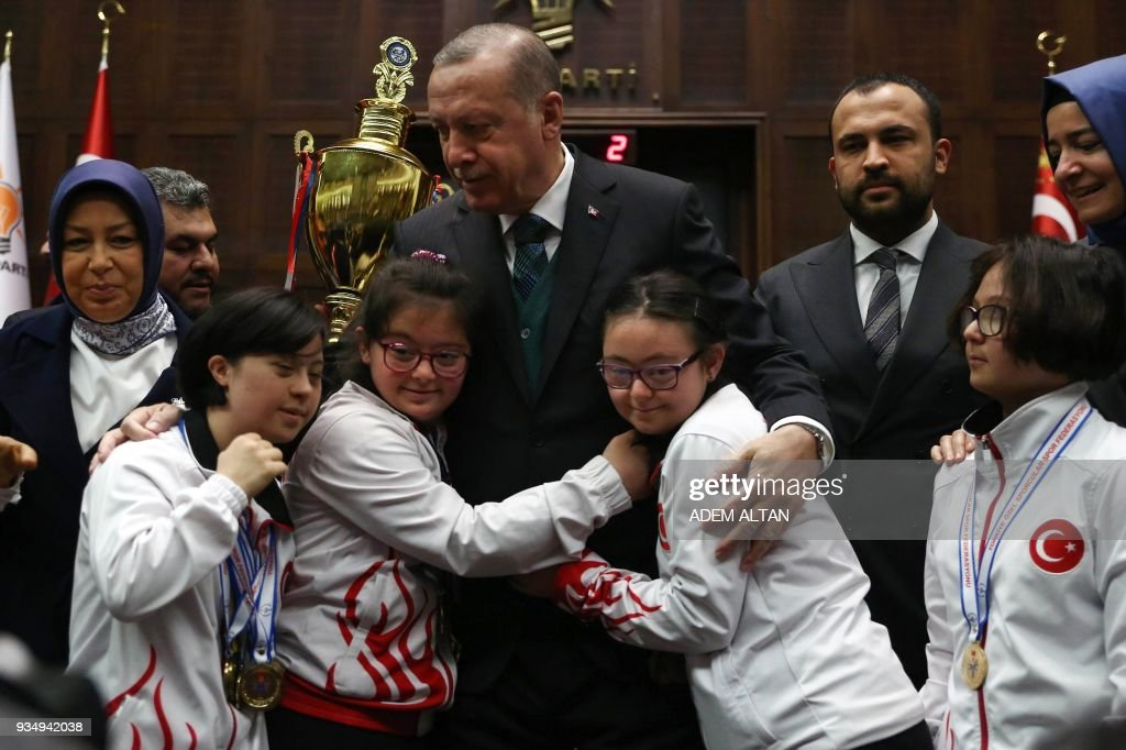 Turkish President and leader of the Justice and Development Party (AK Party) Recep Tayyip Erdogan (C) meets children with Down Syndrome, on the eve of the World Down Syndrome Day, following his speech at the AK Party's parliamentary group meeting at the Grand National Assembly of Turkey (TBMM) in Ankara on March 20, 2018. /