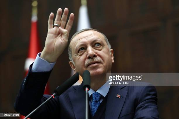 Turkish President and leader of the Justice and Development Party Recep Tayyip Erdogan greets the audience by making the fourfingers Rabia sign as he...