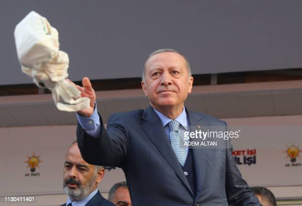 Turkish President and leader of Turkey's ruling Justice and Development Party Recep Tayyip Erdogan throws bags of tea to his supporters during his...