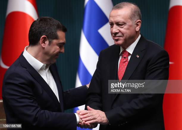 Turkish President Recep Tayyip Erdogan and Greek Prime Minister Alexis Tsipras shake hands at the end of a joint press conference following a meeting...