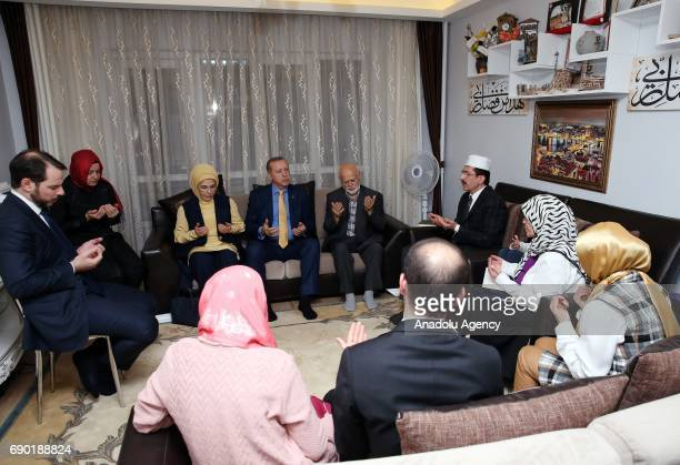 Turkish President Recep Tayyip Erdogan and his wife Emine Erdogan pray after a fast breaking meal with relatives of Cuma Dag who was martyred at...
