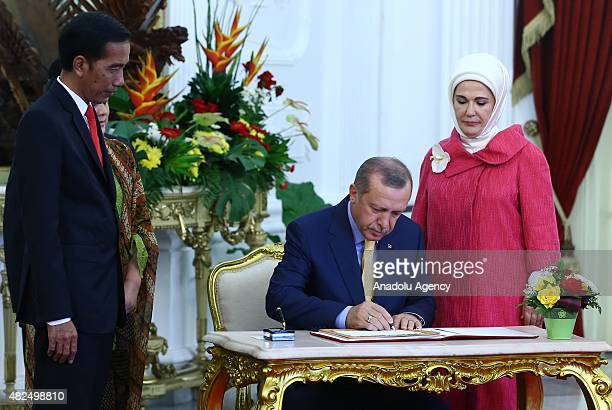 Turkish President Recep Tayyip Erdogan and his wife Emine Erdogan sign guestbook during an official visit at the presidential palace in Jakarta...